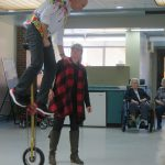Man riding a very tall unicycle while being assisted by a lady.