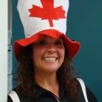 Photo of a woman wearing a red and white hat with the Canadian maple leaf.