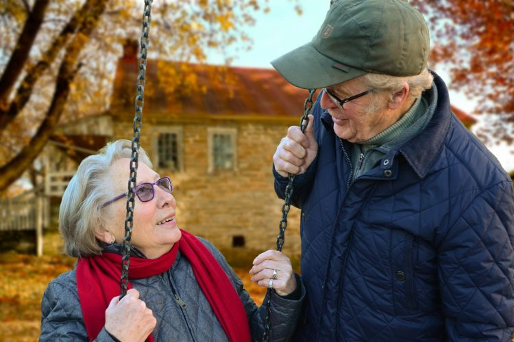 Older woman on a swing gazing upon an older man